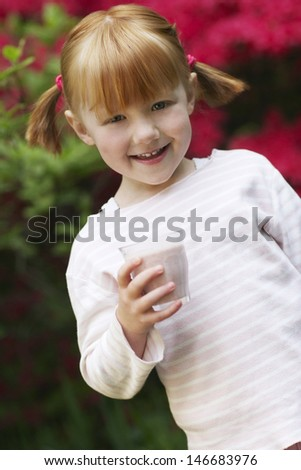 Portrait of happy little girl holding smoothie glass at yard - stock photo