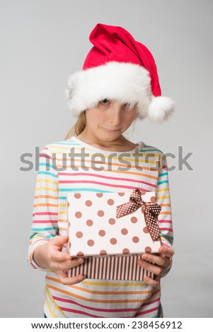 Portrait of happy little girl in santa hat with gift box  - stock photo