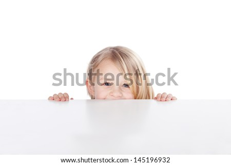 Portrait of happy little girl peeking over table isolated over white background - stock photo