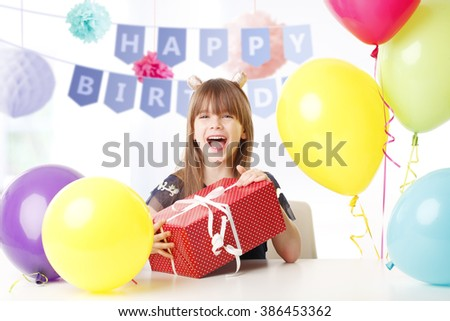 Portrait of happy little girl  with gift box sitting and celebrating her birthday.