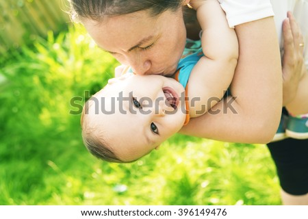 Portrait of happy little mom kissing and shake son outdoors on green summer garden with fresh green grass background Cute latin hispanic mother embracing baby boy looking at camera - stock photo