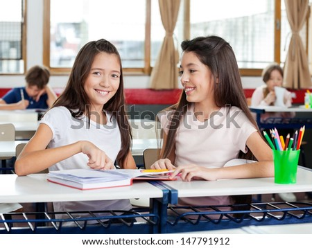 Portrait of happy little schoolgirl sitting with friend at desk and classmates in background - stock photo