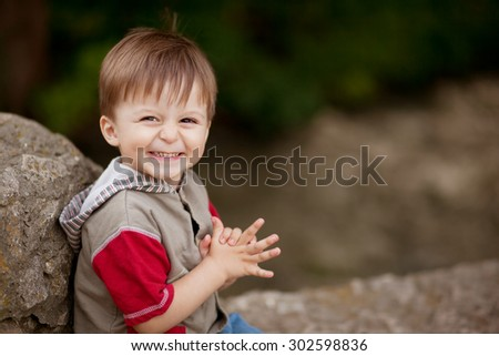 Portrait of happy little shy boy sitting on a stone with blank space on right - stock photo