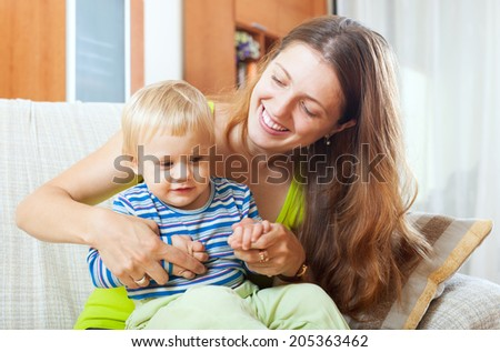 Portrait of happy long-haired mother with toddler on sofa in home - stock photo