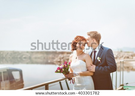 Portrait of happy loving couple, near the shore, smile, communicate, laugh. In the hands of a Bridal bouquet with white, purple, pink flowers