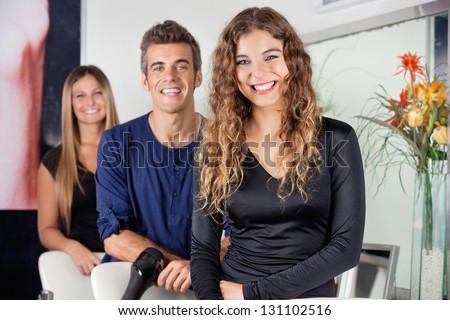 Portrait of happy male and female hairdressers standing in salon - stock photo