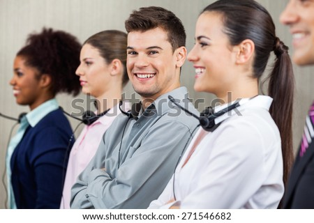 Portrait of happy male call center employee standing in row with colleagues at office - stock photo