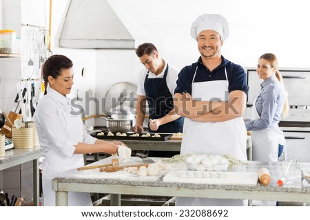 Portrait of happy male chef standing arms crossed while colleagues preparing pasta in commercial kitchen - stock photo
