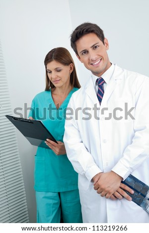 Portrait of happy male dentist with assistant holding clipboard in clinic - stock photo