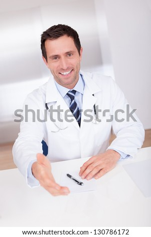 Portrait Of Happy Male Doctor Giving Hand For Handshaking - stock photo
