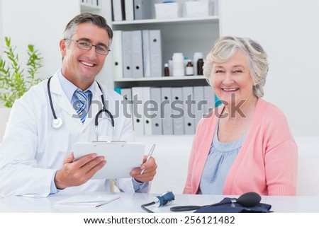 Portrait of happy male doctor holding clipboard while sitting with senior patient in clinic - stock photo