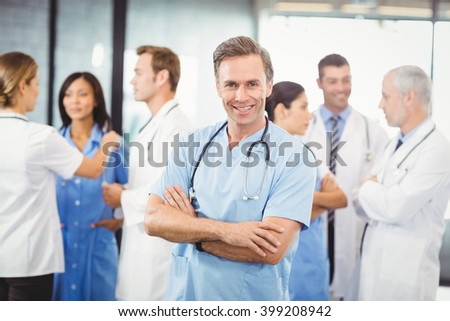 Portrait of happy male doctor standing with arms crossed and colleagues standing behind and discussing in hospital