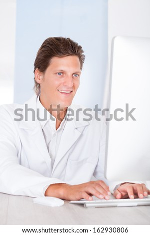 Portrait Of Happy Male Doctor Typing On Keyboard - stock photo