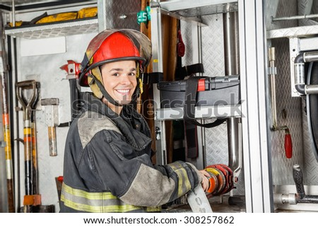 Portrait of happy male firefighter fixing water hose in truck at fire station - stock photo