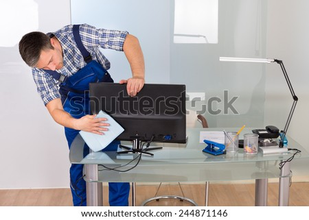 Portrait Of Happy Male Janitor Cleaning Computer On Office Desk