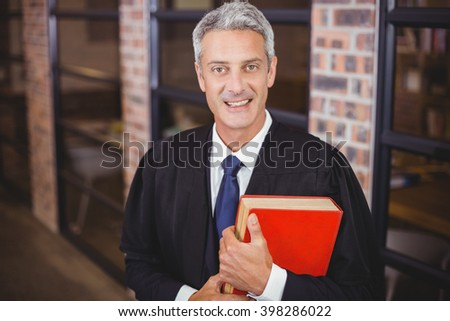Portrait of happy male lawyer standing with red book at office