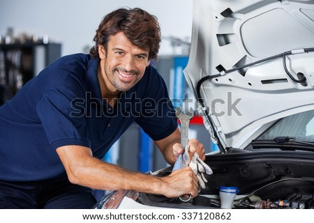 Portrait of happy male mechanic leaning on car with open hood at garage - stock photo