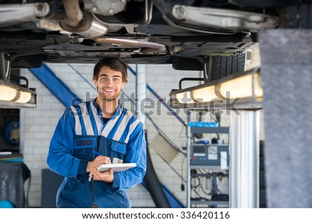 Portrait of happy male mechanic writing on clipboard under car in garage - stock photo