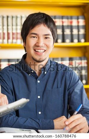 Portrait of happy male student sitting against bookshelf in university library - stock photo