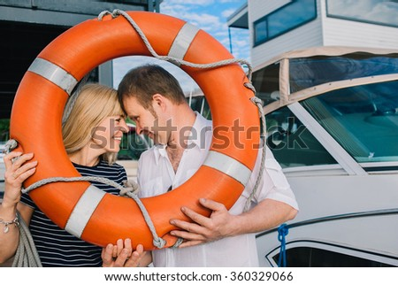 Portrait of happy man and woman holding frame made of life-buoy in yacht club on a summer day. They are a seniour couple in love over 50. - stock photo