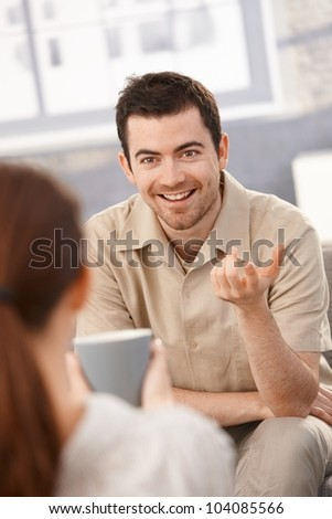 Portrait of happy man chatting with woman at home, sitting in living room. - stock photo
