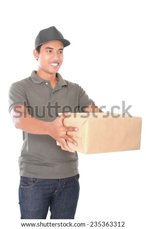 portrait of happy man courier in grey uniform stretch out his arm delivering packages isolated on white background - stock photo