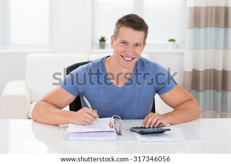 Portrait Of Happy Man Doing Calculation At Home