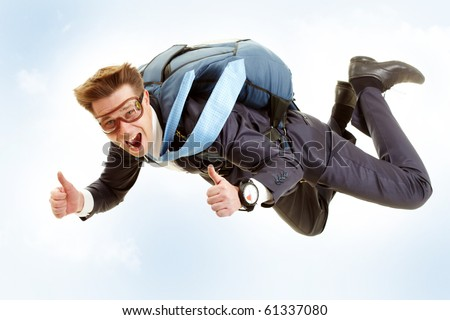 Portrait of happy man flying with parachute and showing thumbs up - stock photo