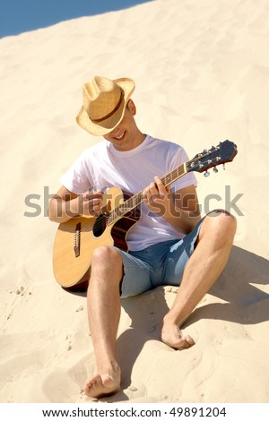 Portrait of happy man in cowboy hat playing the guitar on sandy beach