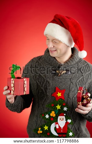 Portrait of happy man in Santa cap looking at toy snake in open giftbox - stock photo