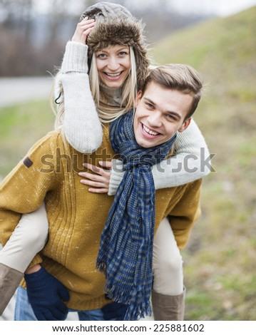 Portrait of happy man piggybacking woman in park - stock photo