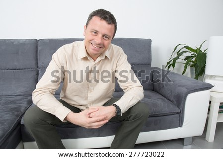 Portrait of happy man sitting on sofa in house