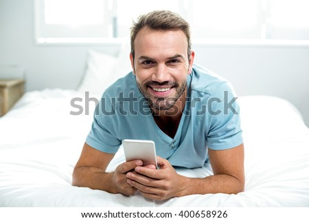 Portrait of happy man using cellphone on bed at home - stock photo