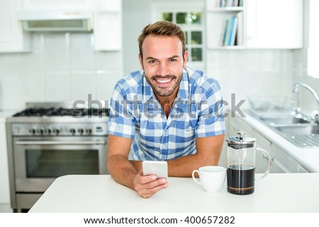 Portrait of happy man using mobile phone while leaning on table in kitchen - stock photo
