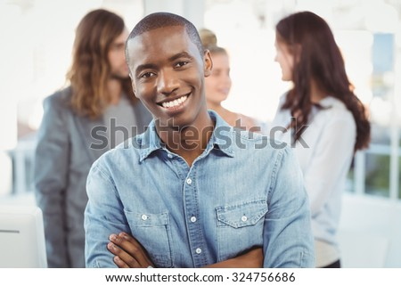 Portrait of happy man with arms crossed while coworkers discussing at office - stock photo