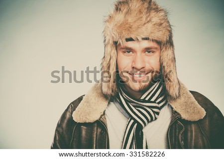 Portrait of happy man with half shaved face beard hair in fur hat and scarf. Smiling handsome guy on blue. Skin care hygiene and winter fashion. Instagram filter. - stock photo
