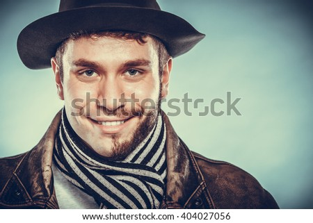 Portrait of happy man with half shaved face beard hair in hat and scarf. Smiling handsome guy on blue. Skin care hygiene and fashion. Instagram cross filter. - stock photo
