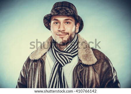 Portrait of happy man with half shaved face beard hair in hat, scarf and jacket. Smiling handsome guy on blue. Skin care hygiene and fashion. Instagram cross filter. - stock photo
