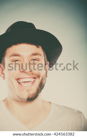 Portrait of happy man with half shaved face beard hair in hat. Smiling handsome guy on blue. Skin care hygiene and fashion. Instagram cross filter. - stock photo