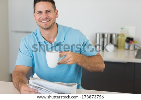 Portrait of happy man with newspaper holding coffee cup at table in house - stock photo