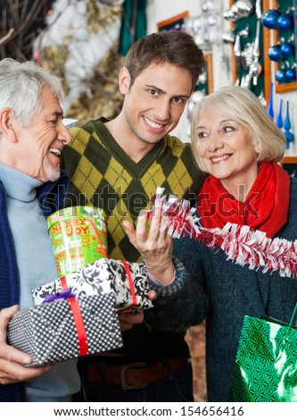 Portrait of happy man with parents shopping for decorations in Christmas store - stock photo