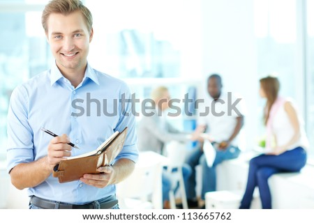 Portrait of happy man with pen and notepad looking at camera in working environment