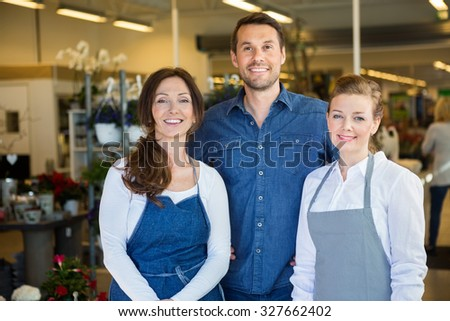 Portrait of happy man with salesgirls in flower shop - stock photo