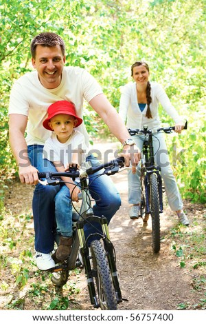 Portrait of happy man with son riding a bicycle in park on background of pretty woman - stock photo