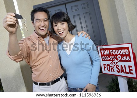 Portrait of happy man with woman holding keys of their new home - stock photo