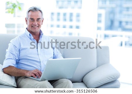 Portrait of happy man working on laptop at home - stock photo