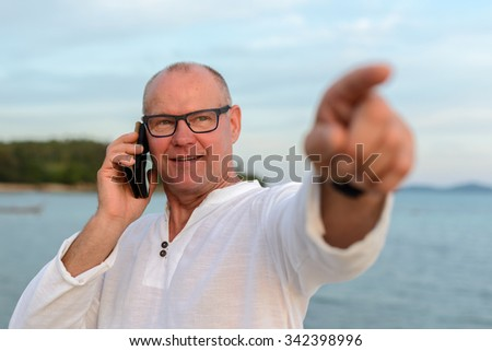 Portrait of happy mature adult man outdoors using mobile phone and pointing finger