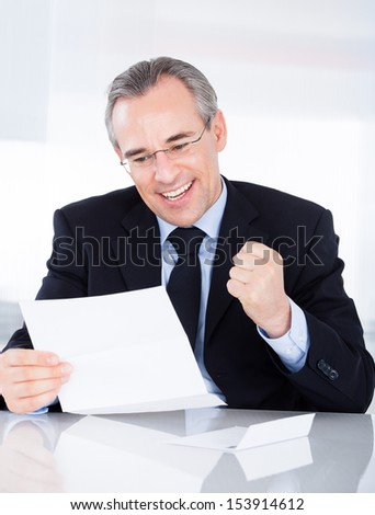 Portrait Of Happy Mature Businessman Holding Document - stock photo