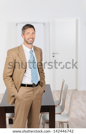 Portrait of happy mature businessman with hands in pockets standing in office - stock photo
