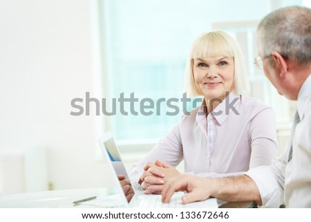 Portrait of happy mature businesswoman looking at camera with her partner near by - stock photo